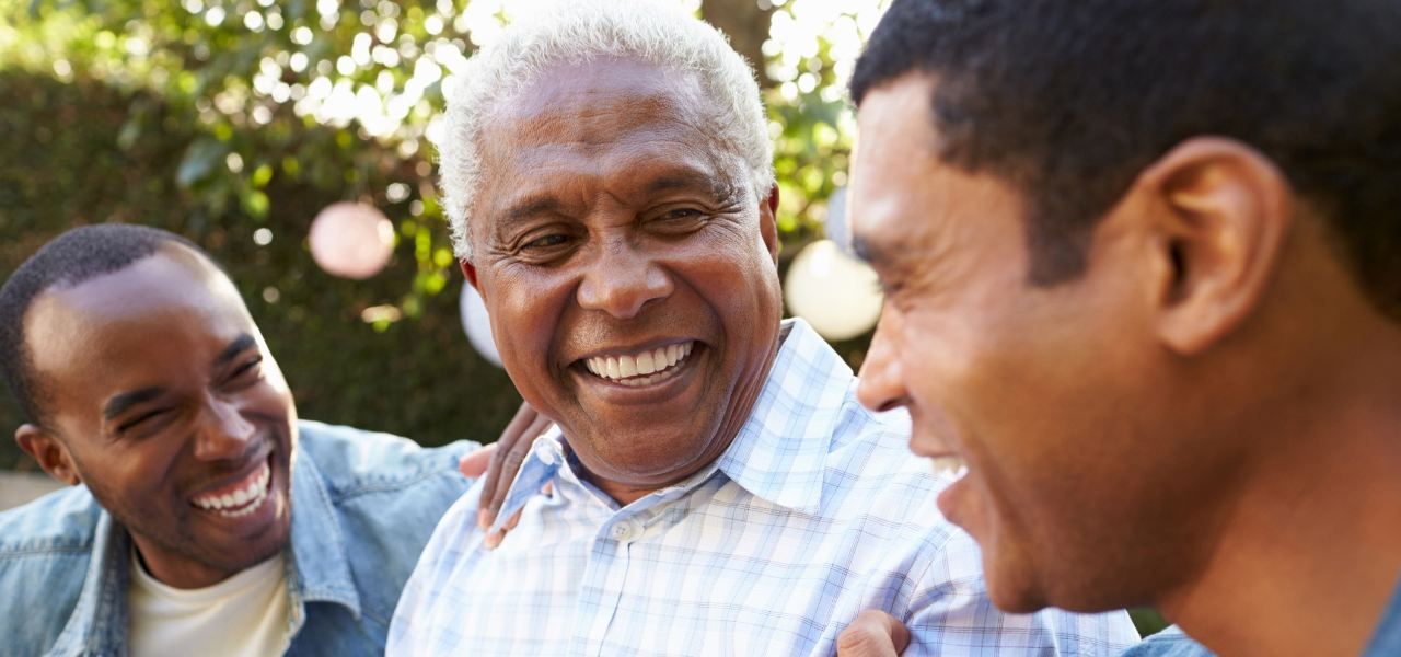 An elderly father laughs alongside his two sons in an outdoor setting