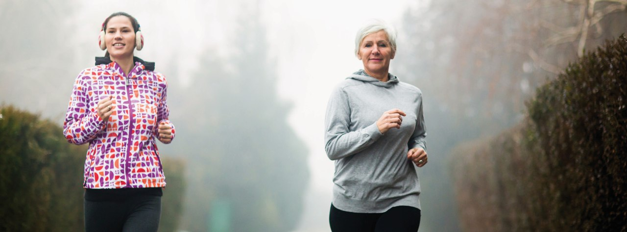 A woman and her daughter jog through a foggy park on a cool autumn day