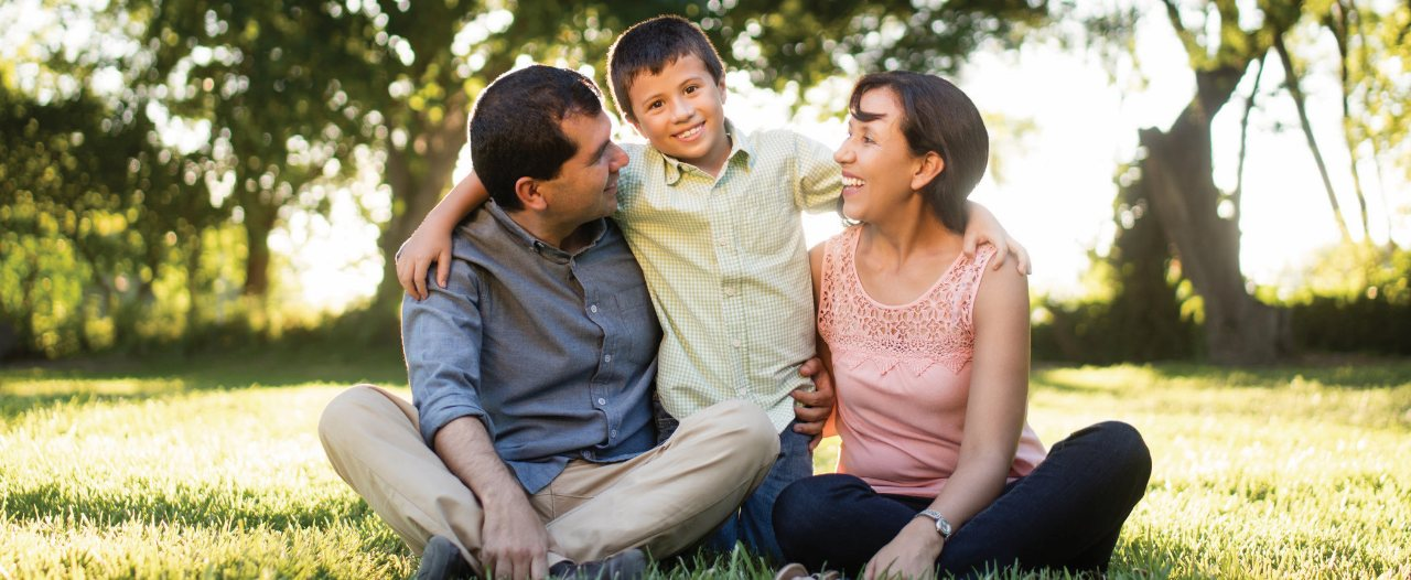 A mother, father and son sit on the grass smiling in a park