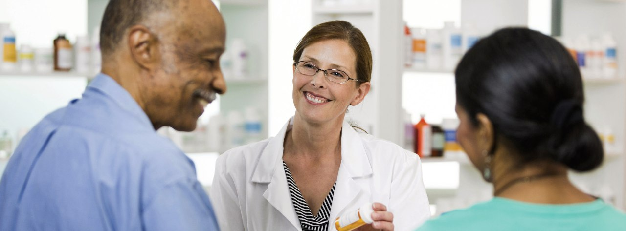A pharmacist speaks with a couple at a pharmacy check out counter