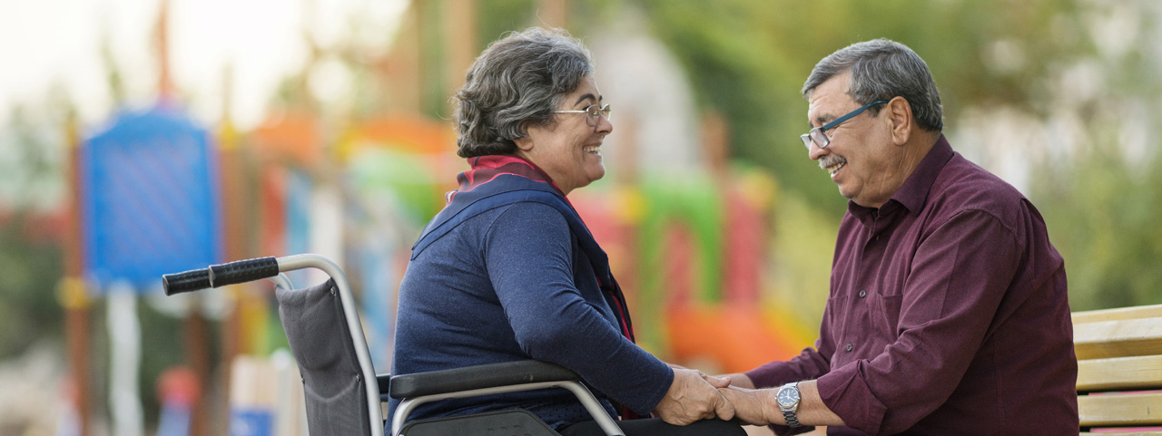 An elderly man and woman hold hands on a park bench