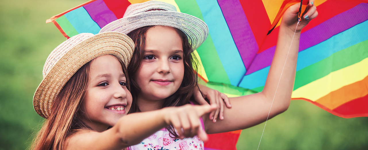 Two young girls get ready to set a rainbow streiped kite to the skies