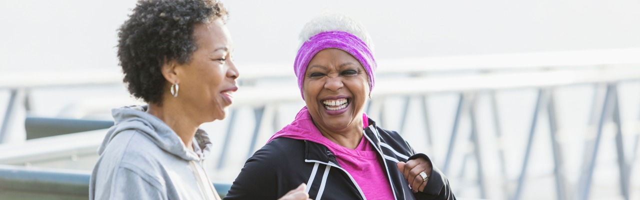 Two older women are jogging in front of a bridge