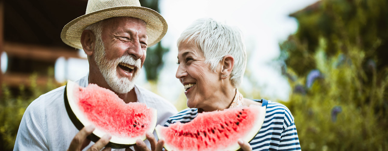 An older man and woman enjoy two large slices of watermelon while laughing