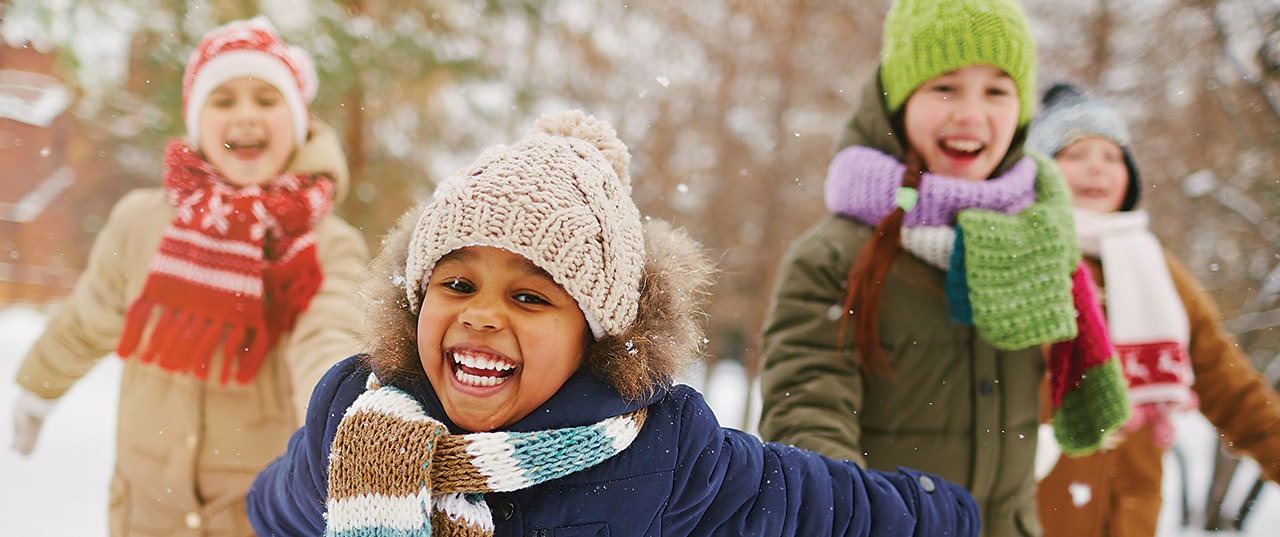 A group of four children smile in their winter clothes in a snowy park
