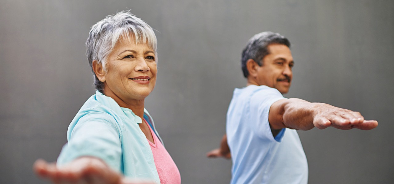 An elderly man and woman engage in light exercise