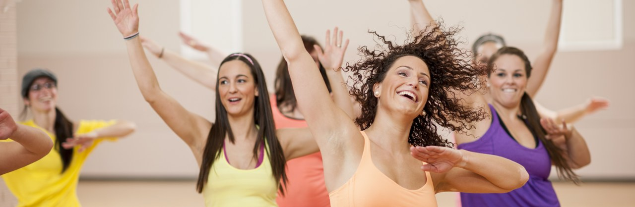 A group of young women raise their arms in an aerobics class