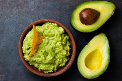 a tortilla chip is stuck in a bowl of guacamole next to two avocado halves