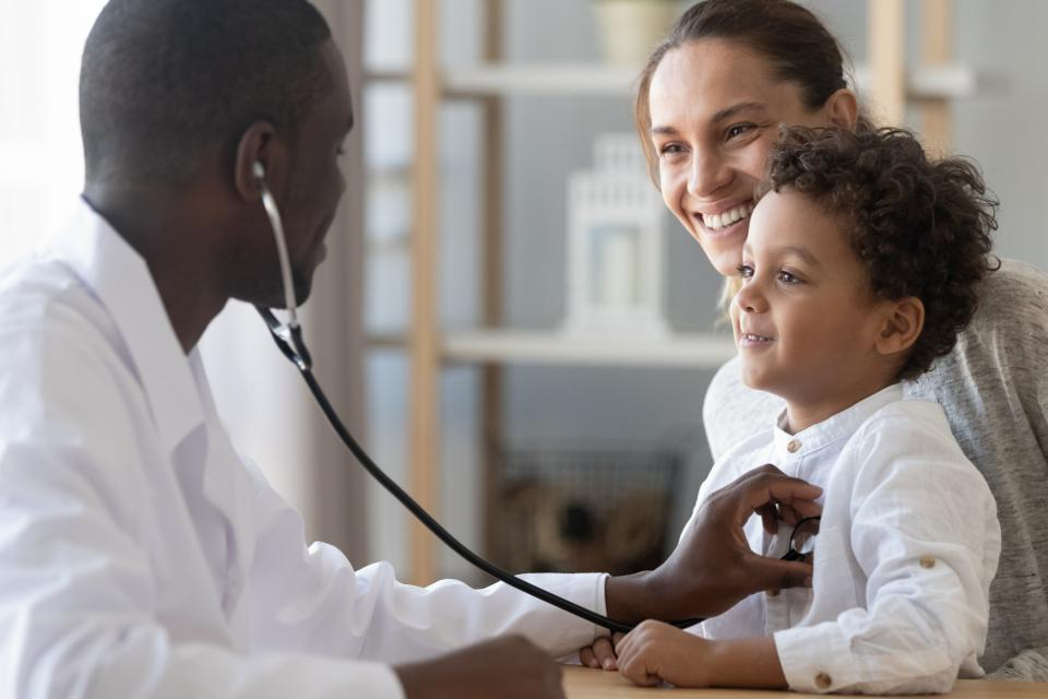 a doctor tends to a child heald by his mother