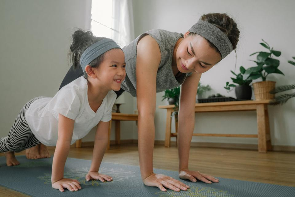 A young mother and her daughter exercise on a yoga mat