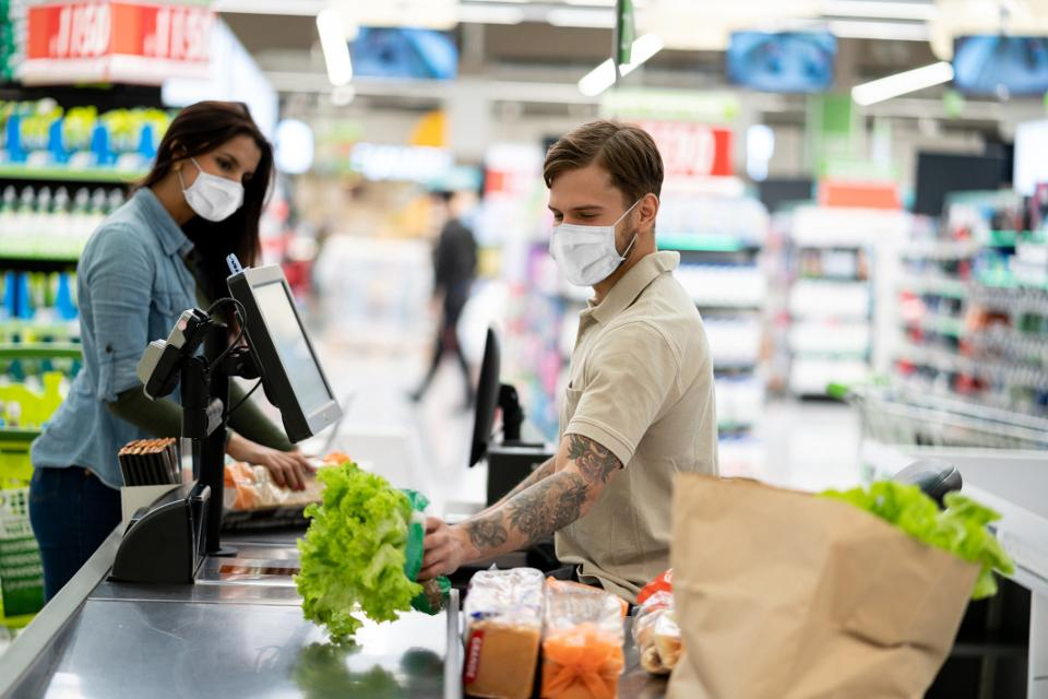 a supermarket cashier scans a woman's groceries while both wear protective face masks